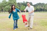 Happy couple playing on the green park with their beautiful daughter