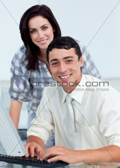 Assertive businesswoman helping her colleague at a computer