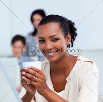 Glowing businesswoman drinking a coffee at her desk