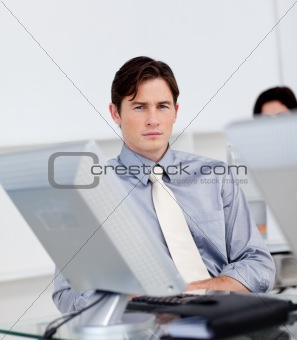 Charming young businessman working at a computer
