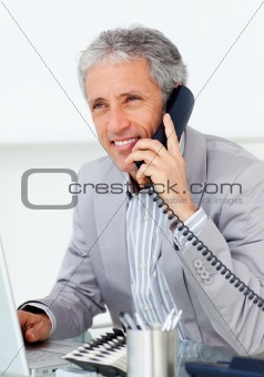 Positive mature businessman talking on phone