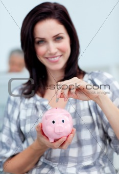 Charismatic businesswoman saving money in a piggy-bank