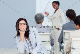 Bored businesswoman yawming at a presentation 