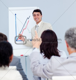 Mature businessman asking a question at a conference