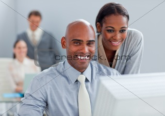 Portrait of two ethnic colleagues working at a computer