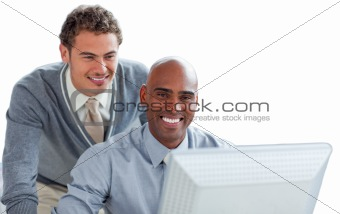 Two young businessmen working at a computer in the