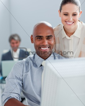 Two positive business colleagues working at a computer