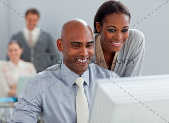 Smiling business partners working at a computer together