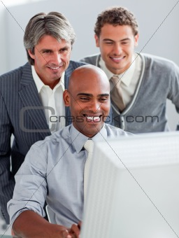 Positive businessmen helping their colleague at a computer