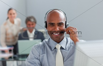 Afro-american  businessman with headset on working at a computer