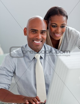 Charming businesswoman helping her colleague at a computer