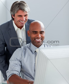 Positive business partners working at a computer together