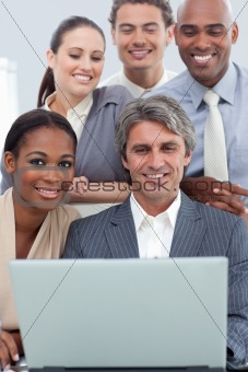 A business group showing ethnic diversity working at a laptop