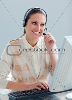 Assertive businesswoman with headset on working at a computer