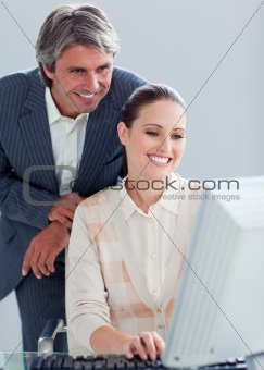 Caucasian manager helping his colleague work at a computer