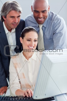 Assertive business people working at a computer