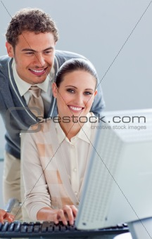 Attentive businessman helping his colleague work at a computer