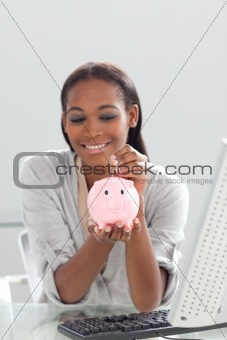 Afro-american businesswoman saving money in a piggybank