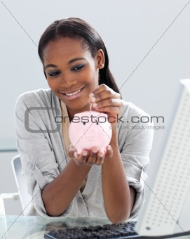 Assertive Afro-american businesswoman saving money in a piggyban
