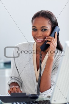 Assertive ethnic businesswoman on phone looking at the camera