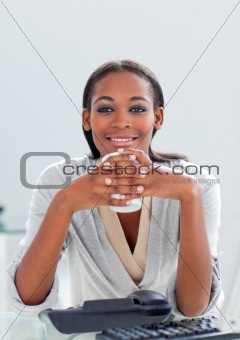 Attractive businesswoman drinking a coffee at her desk