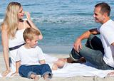 Smiling parents with their son sitting on the sand