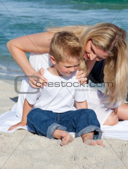 Attentive mother with her son sitting on the sand