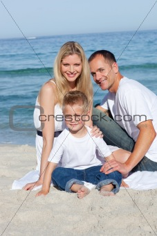 Portrait of cheerful parents with their son sitting on the sand