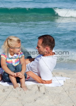 Adorable little girl and her father sitting on the sand