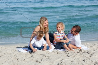 Caring parents with their children sitting on the sand
