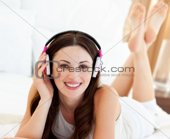 Beautiful woman listening music lying on bed