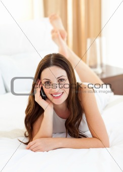 Charming woman on phone lying on bed