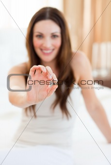 Attractive woman taking a pill sitting on bed