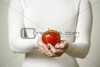 Female hands holding apple