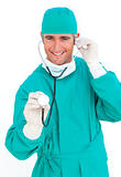 Charismatic surgeon wearing surgical gloves against a white background