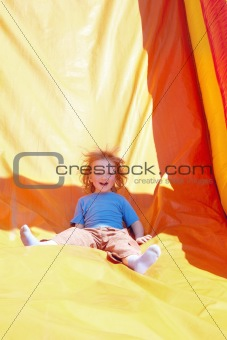 happy little boy enjoying a ride down the slide in amusement park