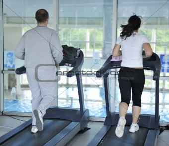 people running on threadmill at fitness club