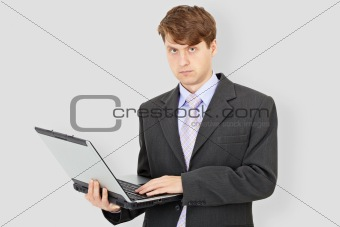 Business man with laptop on grey background