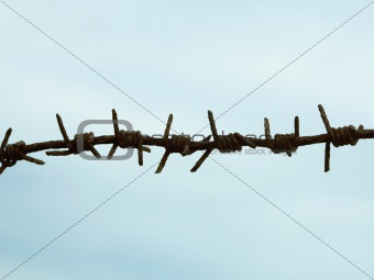 Ancient rusty barbed wire against sky