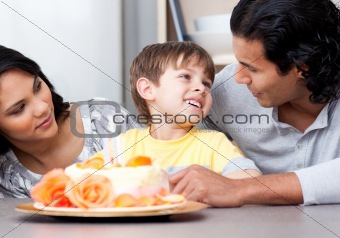 Adorable children celebrating his birthday with his parents in the kitchen