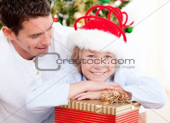 Attractive father opeing present with his son at christmas time