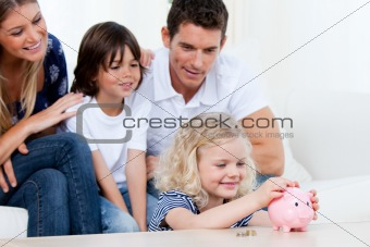 Adorable little girl inserting coin in a piggybank in the living room