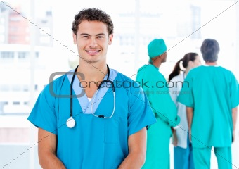 Handsome male doctor looking at the camera while his medical par