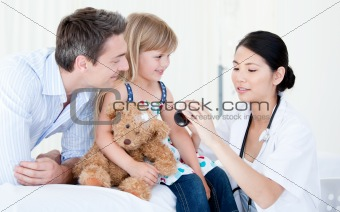 Concentrated asian female doctor giving syrup to a little girl