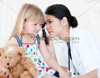 Asian doctor examining little girl with medical equipment