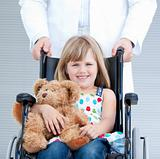 Portrait of a little girl sitting on the wheelchair supported by