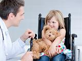 Smiling little girl sitting on the wheelchair lokking at the doc