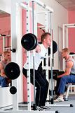 young man lifting heavy bar-bell in modern gym