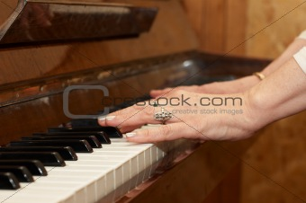A caucasian woman's hand playing a keyboard