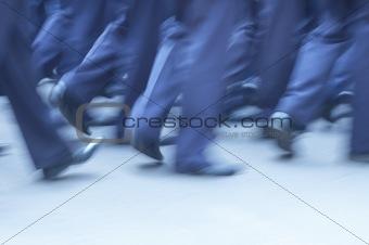 Man in identical suites walking throught street